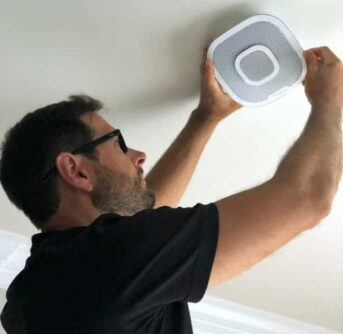 A man installing a smoke detector to the ceiling.