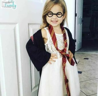 A little girl dresses up as Harry Potter standing in front of a white door.