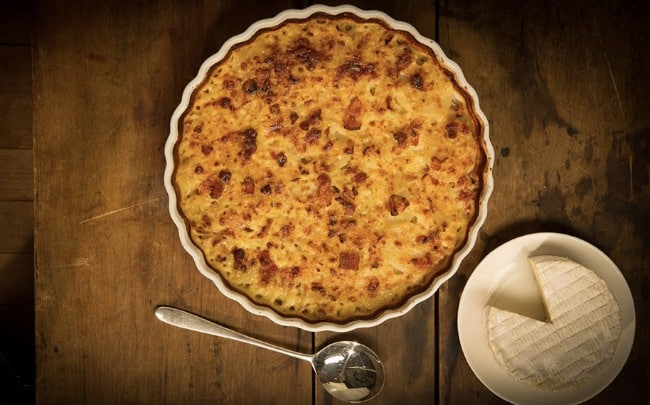 A cheese casserole in a white pan with a cheese circle beside it.