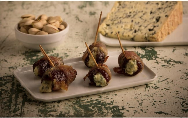 A plate of bacon wrapped cheese balls with tooth picks in them.