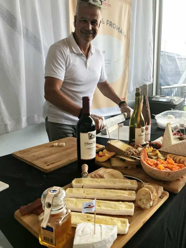 A man preparing food on a table with a variety of wine and cheese.