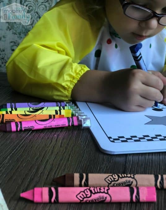 A little girl sitting at a table coloring with crayons.