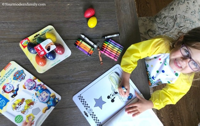 A little girl sitting at a table coloring.