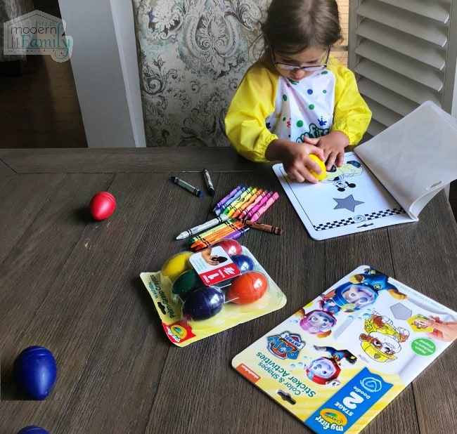 A small child sitting on a table coloring with egg shaped crayons.