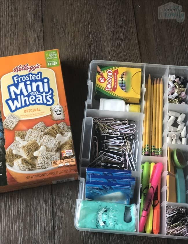 A plastic container of school supplies with a box of cereal beside it.