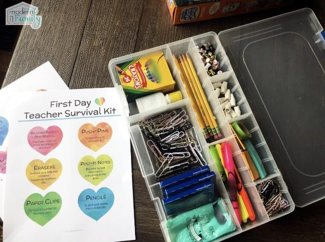 A plastic divided box of  school supplies next to a white paper with colorful hearts on it.
