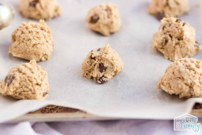 Raw spoonfuls of chocolate chip cookie dough on a cookie pan.