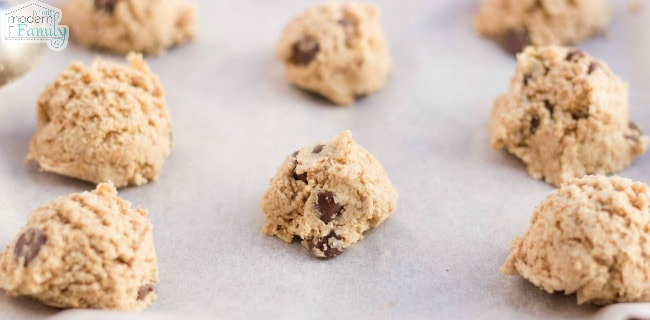 A close up of balls of raw chocolate chip cookie dough on a cookie sheet.