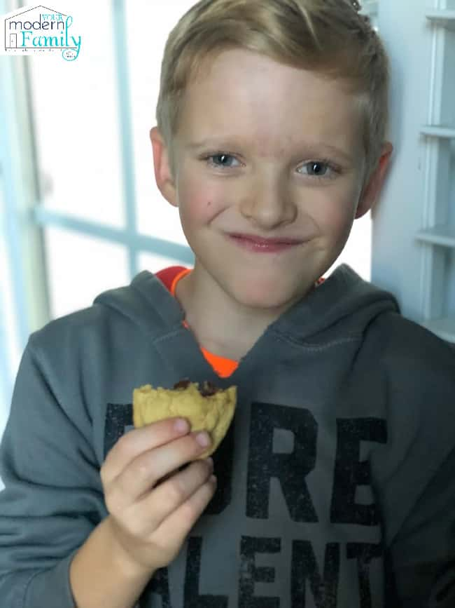 A young boy eating a chocolate chip cookie with a big smile on his face.