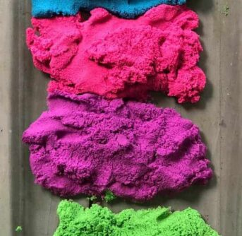 A close up of piles  of kinetic sand in a variety of colors.