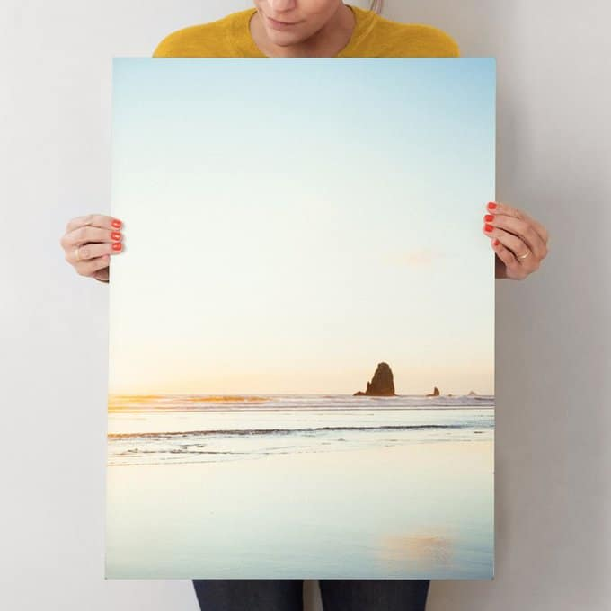 A woman holding a painting of the beach.