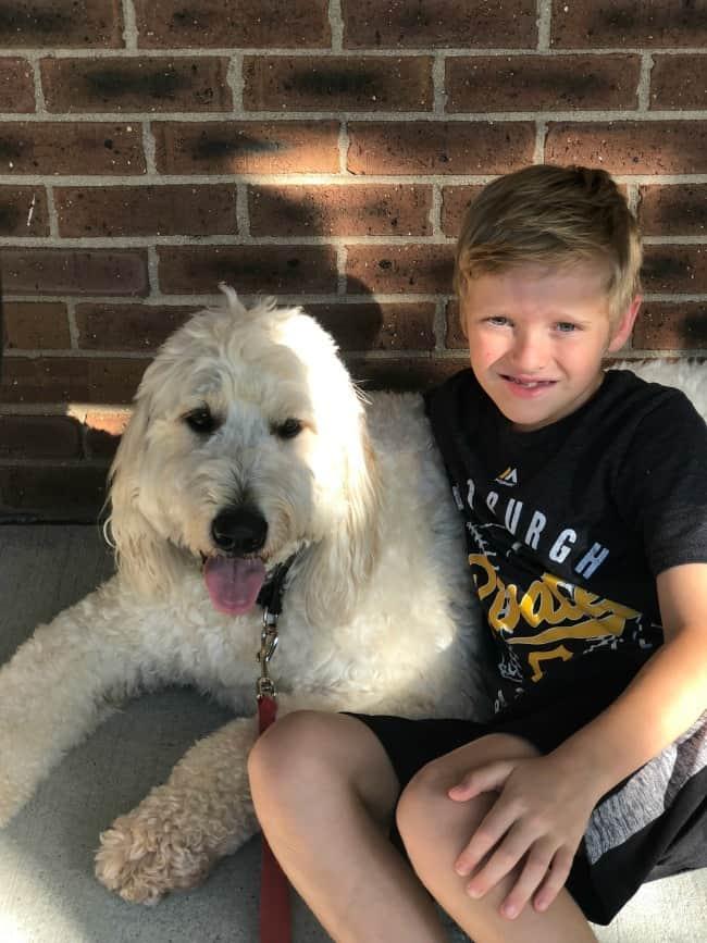 A boy holding a dog.