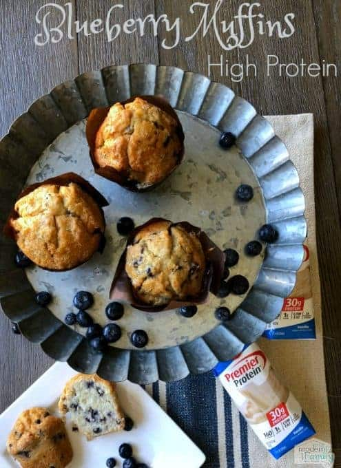 A metal pie pan with three muffins in it with blueberries around them.