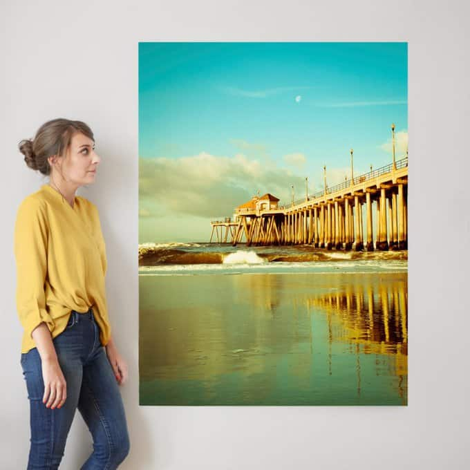 A person standing beside a large painting of a bridge with water going under it.