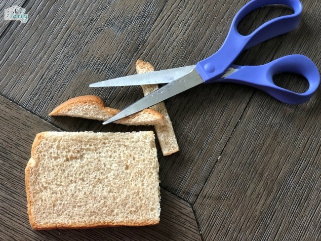 A piece of bread with crest cut off with a pair of scissors beside it.