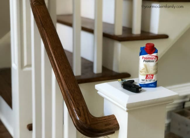A wooden stair railing with a set of keys and a carton of Premier Protein sitting at the bottom.