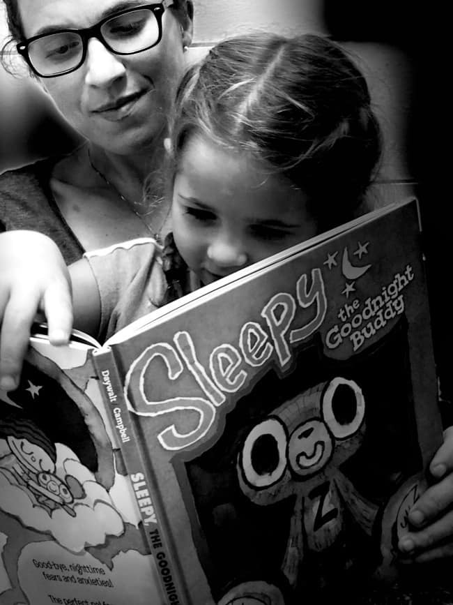 A woman reading a children\'s book to a little girl.