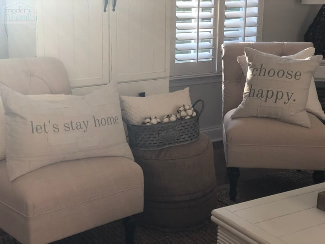 Two white cushioned chairs with pillows on them.