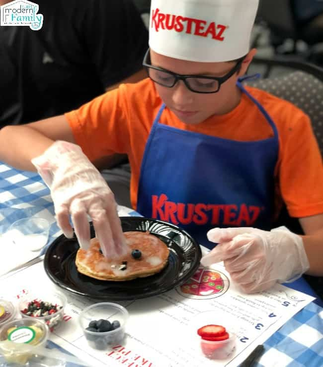 A young boy in a Krusteaz chef hat adding toppings to a pancake.