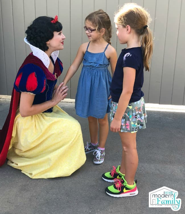 Two girls talking to a Snow White character.