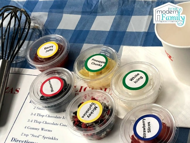 A variety of cups with ingredients on a blue and white checkered table cloth.