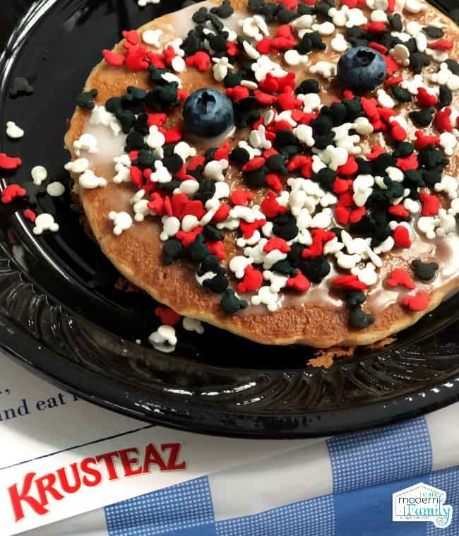 A pancake sitting on a black plastic plate that has been decorated with Mickey Mouse candies.