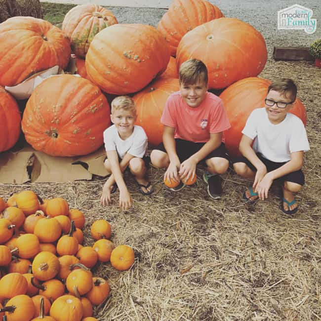 A group of kids kneeling in front of a pile of pumpkins.
