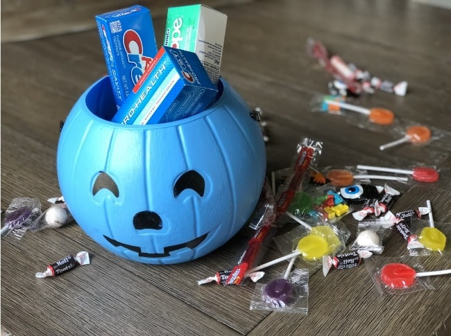 A blue plastic pumpkin with tubes of Crest tooth paste in it with candy spread out on the table.