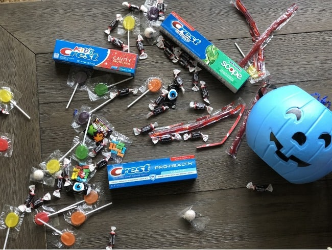 Three tubes of Crest tooth paste lying on a table with a variety of candy  spread around.