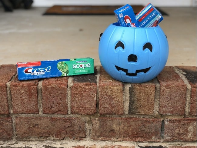 A tube of Crest sitting beside a blue plastic pumpkin with more tubes of  Crest in the pumpkin resting on brick steps.