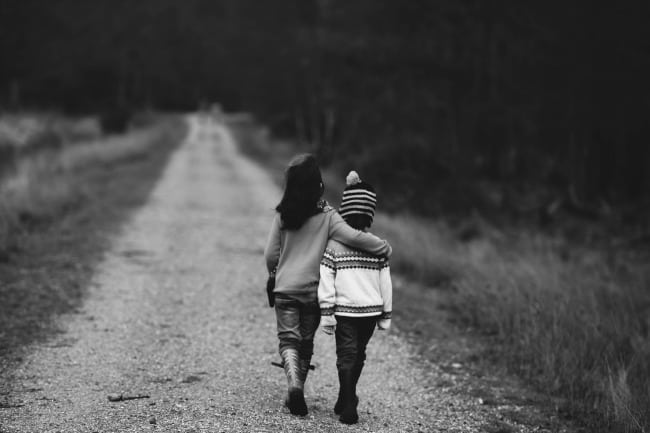 Two kids walking down a dirt road together.
