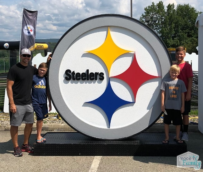 A group of people standing in front of a Pittsburgh Steeler sign.