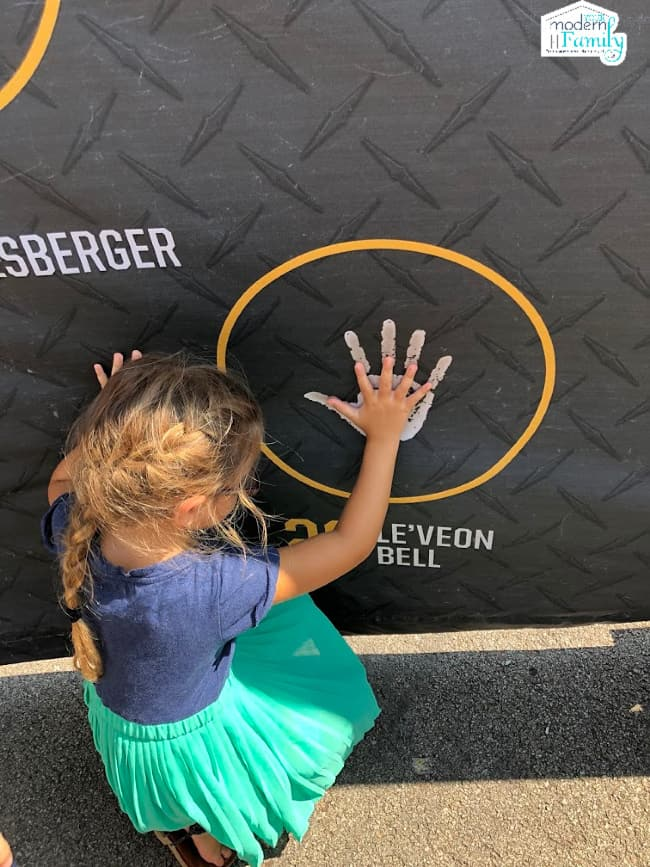 A little girl with her hands on a large hand print that is painted on a football themed wall.