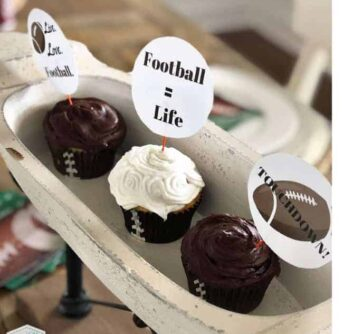 Three cupcakes on a white oval tray with football themed cupcake toppers on them.