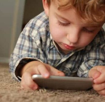 A young boy lying on a carpeted floor looking at a cell phone.