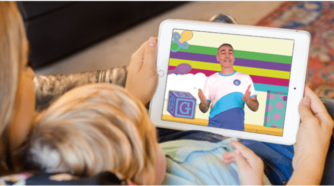 A young boy lying on his back on a couch watching a video on a tablet.