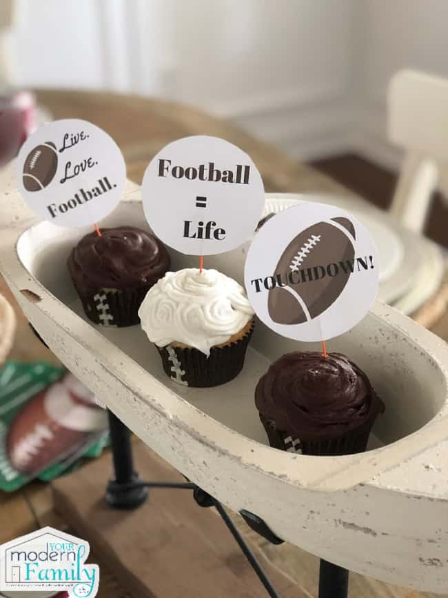 Three cupcakes in an oval tray with football themes cupcake toppers.