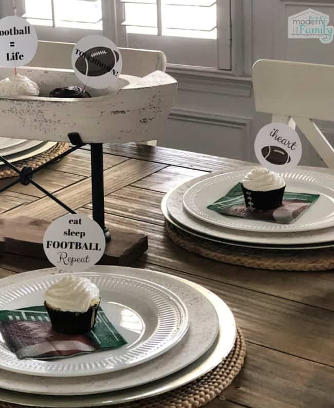 A wooden table set with white dishes with a football napkins and a cupcake with football themed cupcake toppers on them.