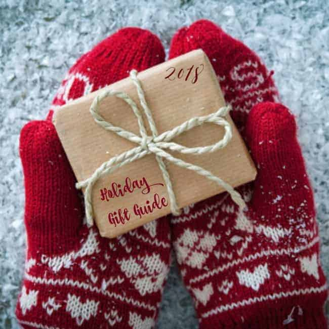A close up of person wearing mittens holding a wrapped present.