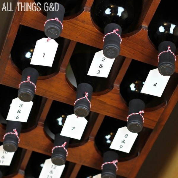 A wooden wine rack holding numerous bottles of wine with tags attached to the neck of each bottle.