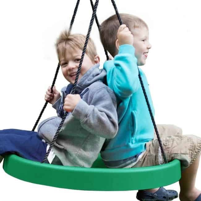 Two  small children sitting  back to back on a  round plastic swing.
