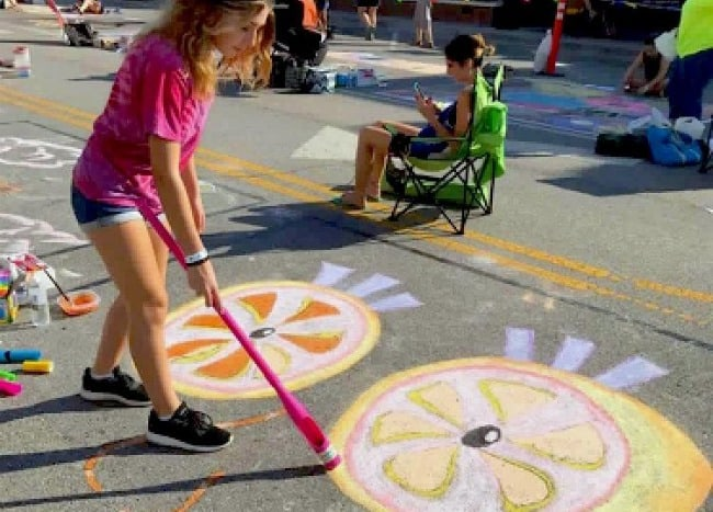 A little girl using chalk to color on the cement.