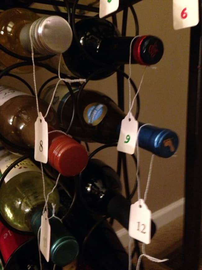 A close up of a metal wine rack holding wine bottles with numbered tags hanging from each bottle.