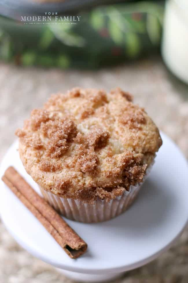 A close up of a muffin sitting on a white plate with a stick of cinnamon sitting beside it.