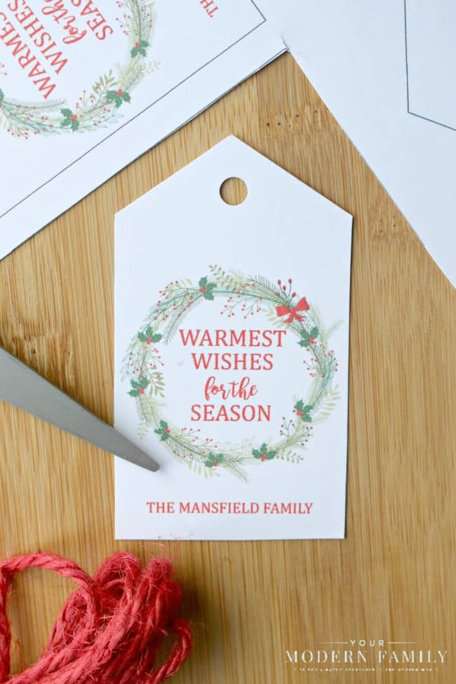 A close up of a gift tag with scissors beside it.