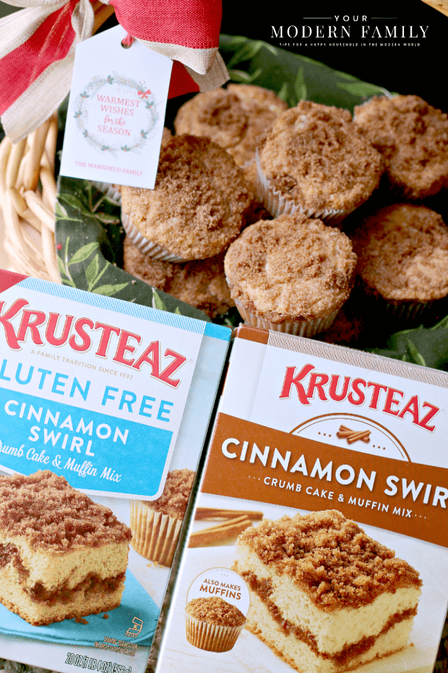 Two boxes of Krusteaz muffin mix in front of a basket of muffins with a gift tag attached.