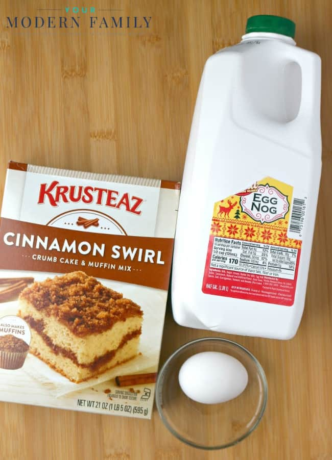 A box of Krusteaz cinnamon swirl mix with an egg and a container of milk beside it.