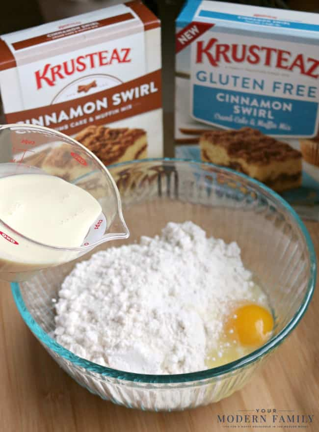 A glass bowl with muffin mix and an egg in it with milk being poured into the bowl and two boxes of Krusreaz in the background.
