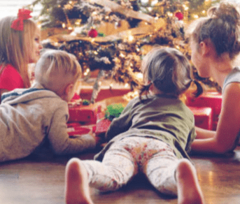 Two children and a woman lying on the floor in front of a Christmas tree.