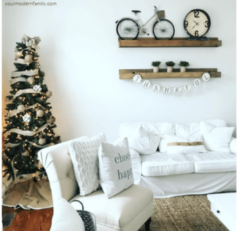 A white chair and couch with wooden shelves above them with a Christmas tree in the background.